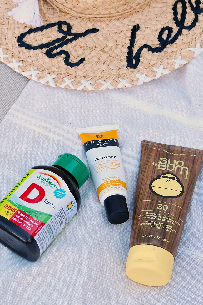 Sun protection tips for summer. Sunscreen and vitamin D bottle on a beach towel.