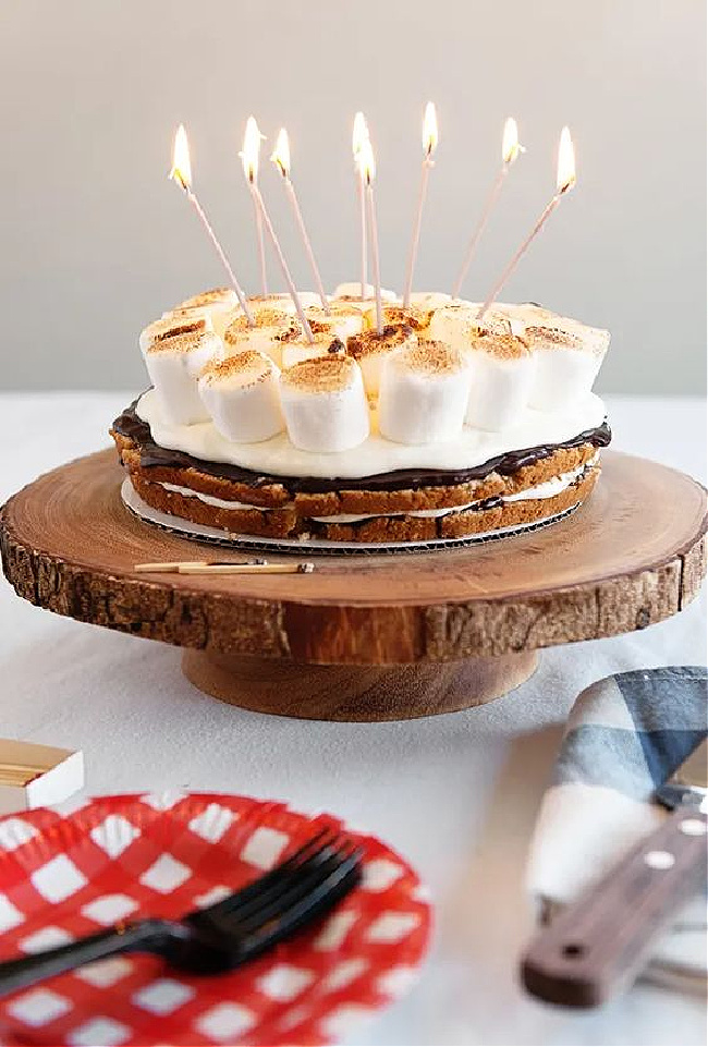 S'mores birthday cake on a wood slice cake plate.
