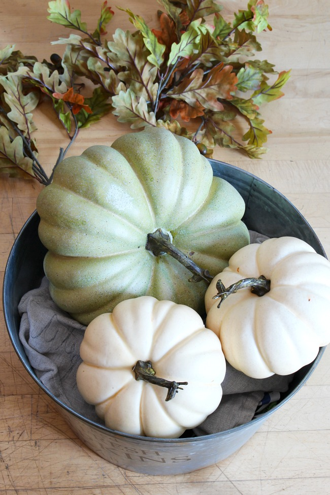 Galvanized metal bucket filled with faux pumpkins.