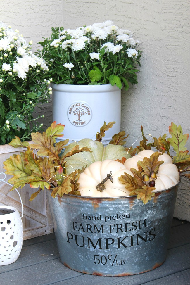 Lighted pumpkin basket. Galvanized metal bucket filled with pumpkins and fall leaves on a fall front porch.