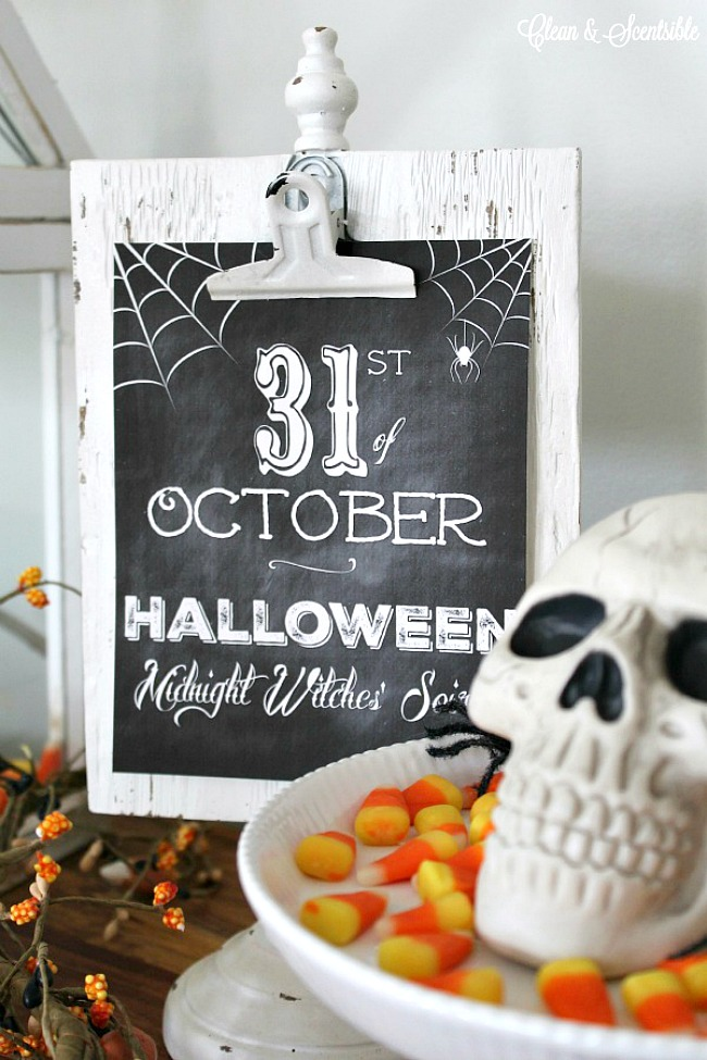 Free chalkboard Halloween printable on a white clipboard with a skull and candy corn.