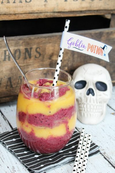 Orange and purple Halloween goblin potion smoothie in a clear glass with a fun straw topper.