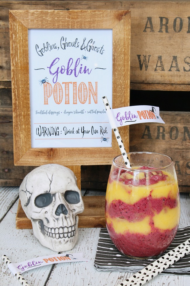 Delicious orange and purple smoothies swirled together for a fun and healthy Halloween treat. Displayed in a clear glass with a goblin potion straw topper.