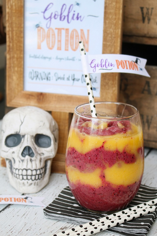 Orange and purple smoothies swirled together in a clear glass. Comes with free goblin potion printables to frame or use as a straw topper.