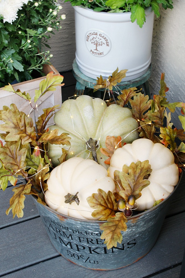 Pumpkins in a galvanized bucket with mini lights and fall leaves.