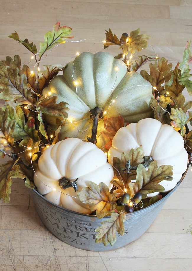 DIY lighted pumpkin basket. Galvanized metal bucket filled with pumpkins, fall leaves, and mini lights.