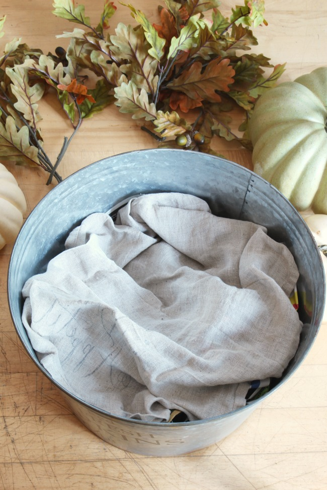 Galvanized metal bucket filled with crumpled newspaper and a linen towel to raise up pumpkins.