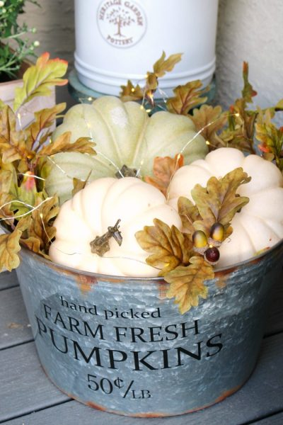 Lighted fall pumpkin bucket. Galvanized metal bucket filled with pumpkins, fall leaves, and mini lights.