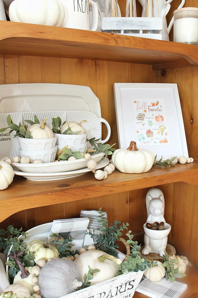 Wood hutch decorated for fall with white pumpkins and greenery. Includes a free fall printable.