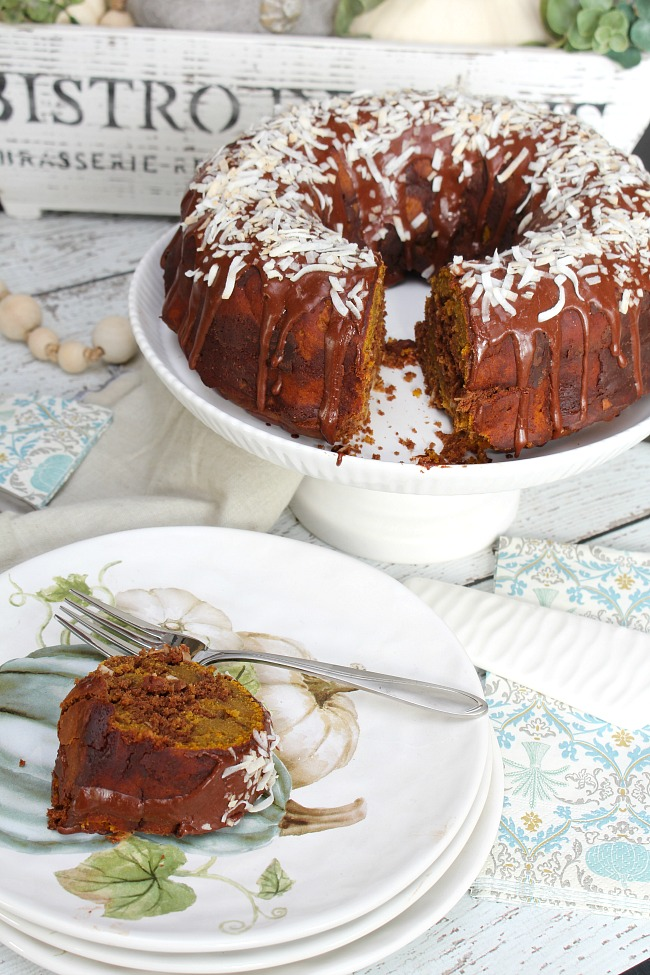 Chocolate coconut pumpkin swirl bundt cake on a cake stand with fall plates.
