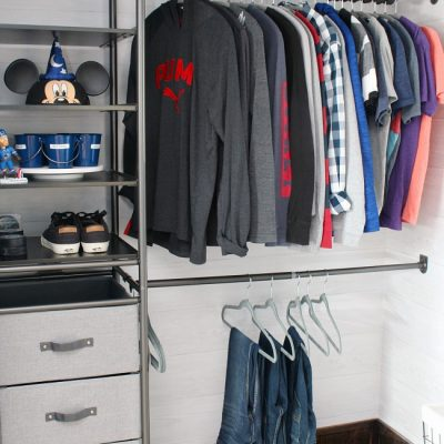 Awesome closet organizer in a teenage boys' closet. Has combination of open storage shelves and closed storage with pull out drawers.