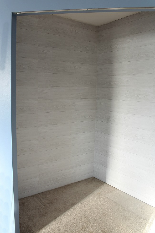 Removeable shiplap wall paper in a clothes closet.