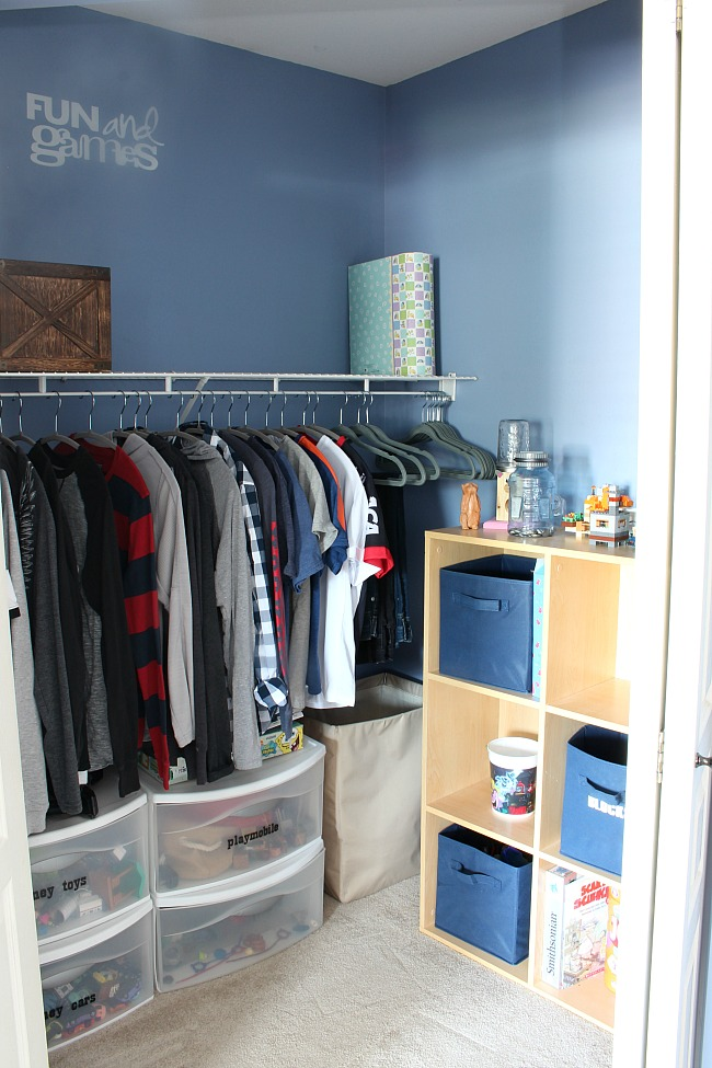 Before photo of a kids' closet with lots of toy storage using cube storage and plastic pull out drawers.