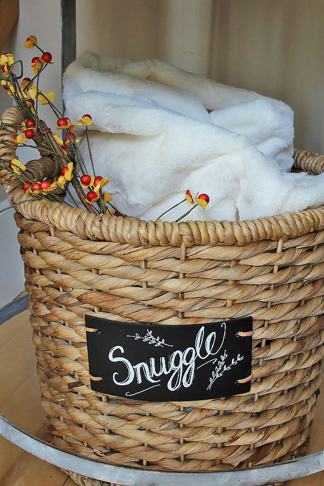 Basket with chalkboard Snuggle label used for throw blanket storage.