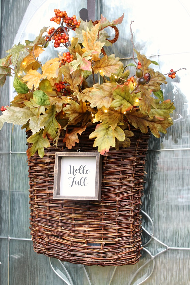 "Fall basket wreath. Wicker basket filled with a variety of fall stems and mini lights. A wood ""hello fall"" sign is attached to the front."
