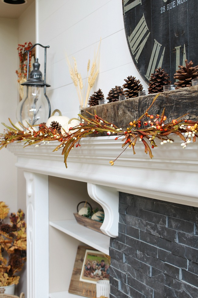 White fall mantel using a sugar mold filled with pinecones and glass candle votives.