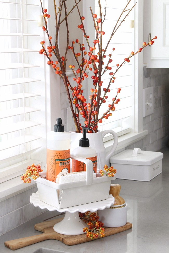 Kitchen dish soap and hand wash in a white ceramic basket beside the sink with faux fall stems.