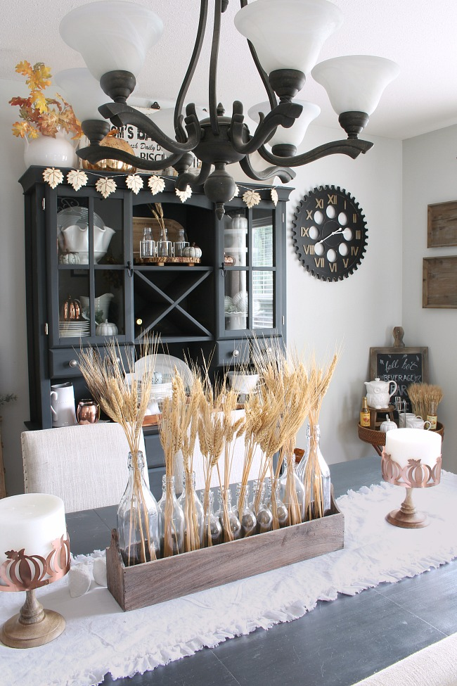 Neutral farmhouse style dining room decorated for fall with wheat centerpiece.
