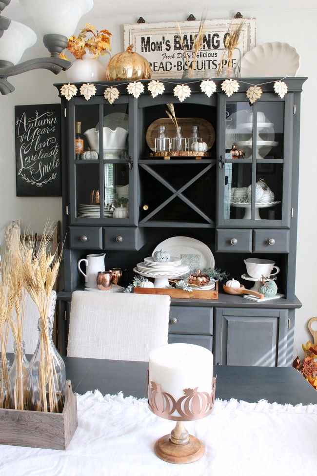 Farmhouse style dining room with painted buffet and hutch. Decorated for fall with neutral colors and natural elements.