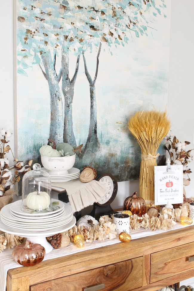 Farmhouse style dining room with wooden sideboard decorated for fall with wheat and other natural elements.