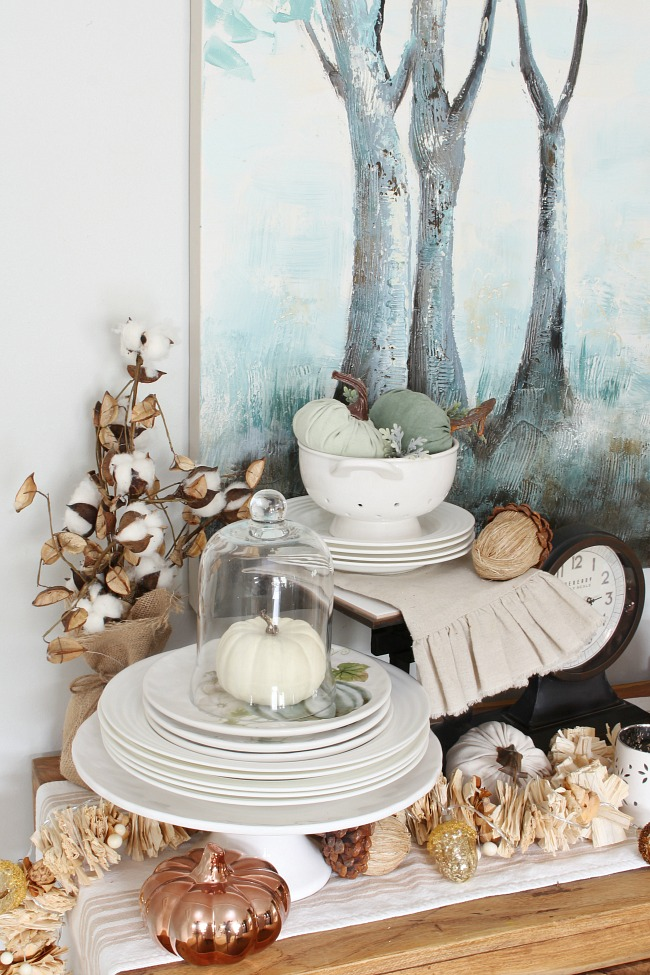 Sideboard with white dishware. Decorated for fall with white pumpkins, copper and natural elements.