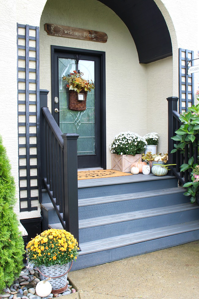 Fall front porch with composite decking. Decorated for fall with heirloom pumpkins and mums.