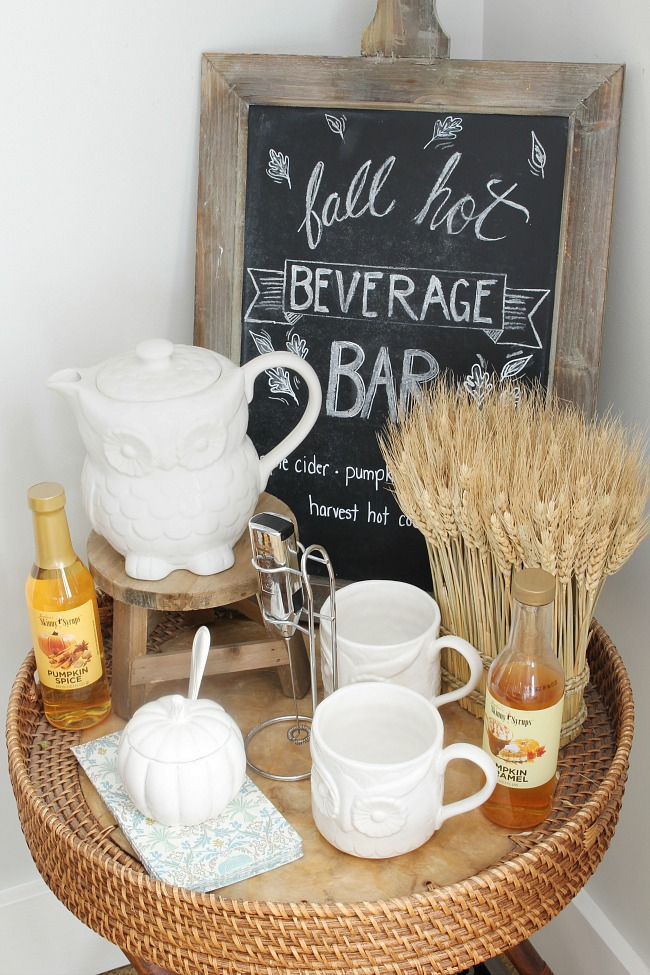 Fall hot beverage bar with chalkboard sign and white ceramic tea pot and fall flavored syrups.