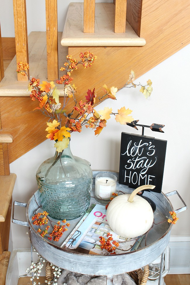 Fall sidetable with fall leaves, a white pumpkin, and a Let's Stay Home chalkboard sign.