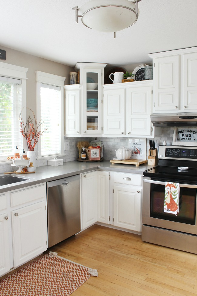 White kitchen decorated for fall with some pops of orange.