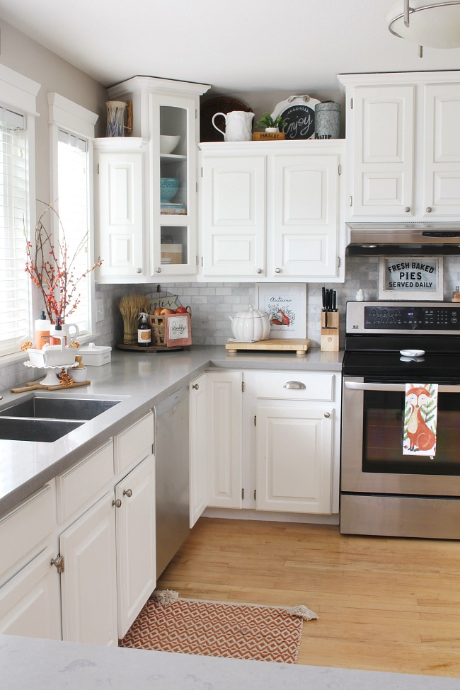 White farmhouse style kitchen decorated for fall with pops of orange.