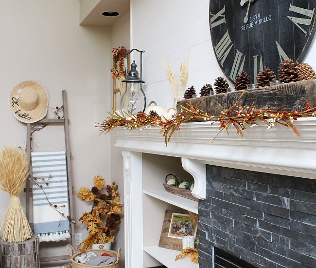 White mantel with faux shiplap decorated for fall. Traditional fall colors, mini-lights and natural elements.