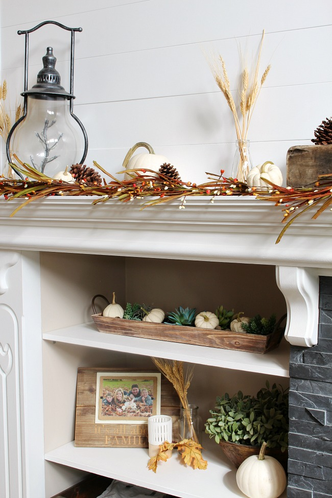 Fall mantel with shelves decorated for fall with white pumpkins.