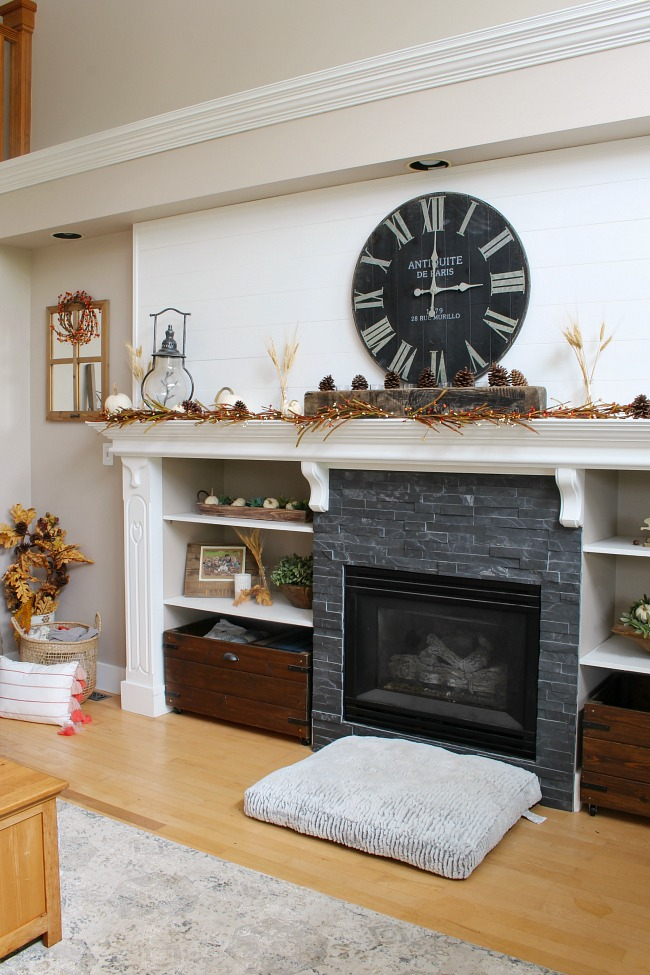 Large white mantel with dark tile. Decorated for fall with traditional fall colors and natural elements.