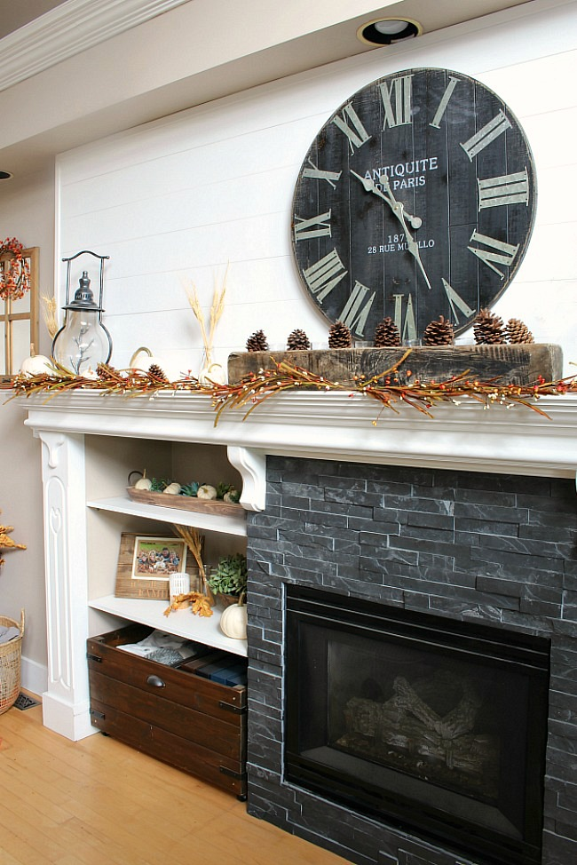 White mantel with dark tile. Decorated for fall with traditional fall colors and natural elements. A weathered wood sugar mold was used in the center.