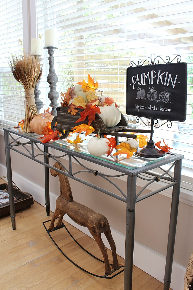Pumpkin patch fall vignette with pumpkins in a wheelbarrow, lighted leaves and a chalkboard sign.