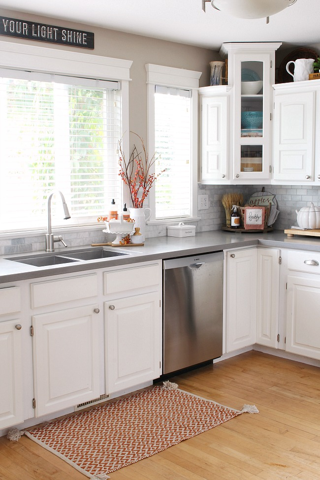 White kitchen with grey quartz countertops decorated for fall with pops of orange.