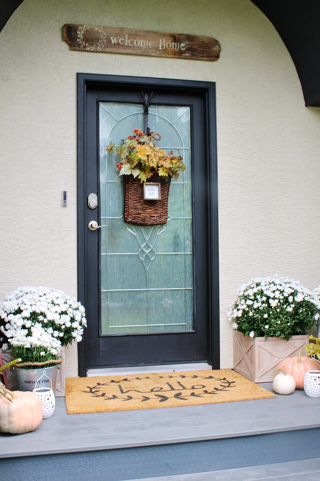 Fall front porch with black door.  Decorated with mums and pumpkins.