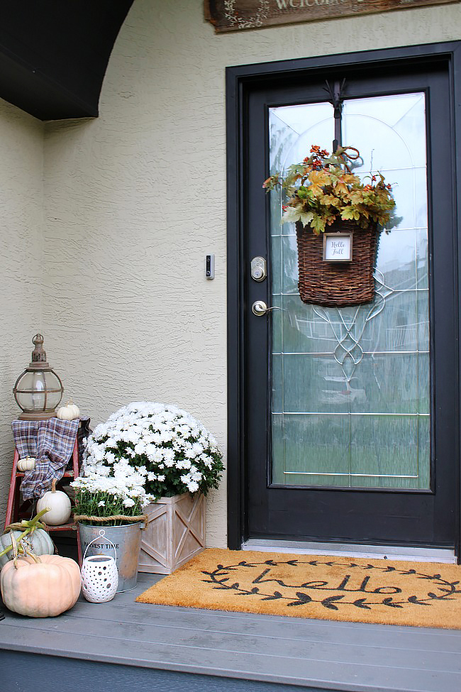 Front porch decorated for fall. Black door with fall basket wreath and lots of pumpkins and white mums.