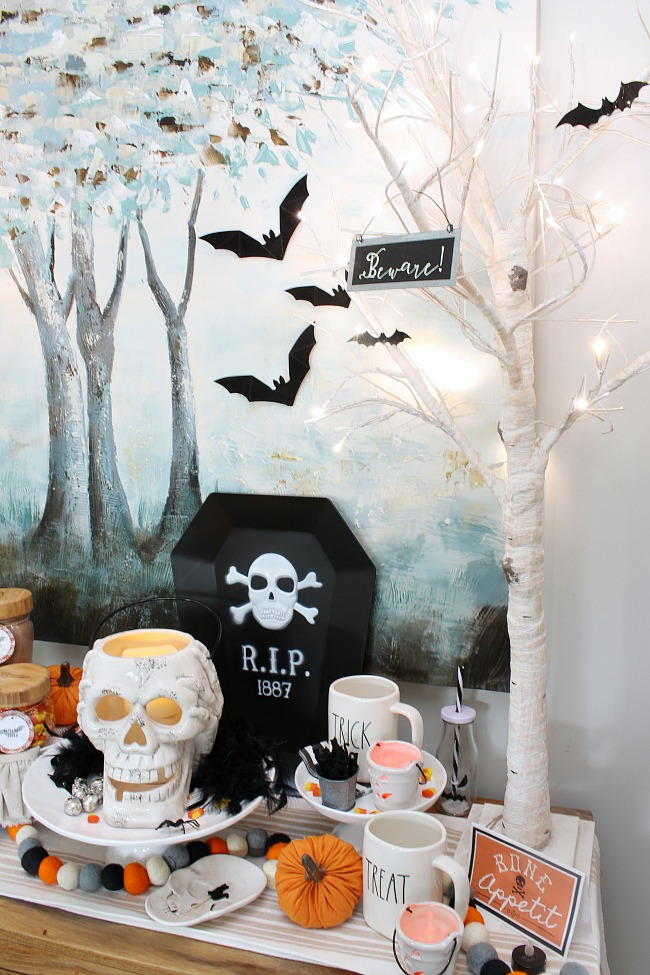 Halloween hot chocolate bar with lighted trees and velvet bats.