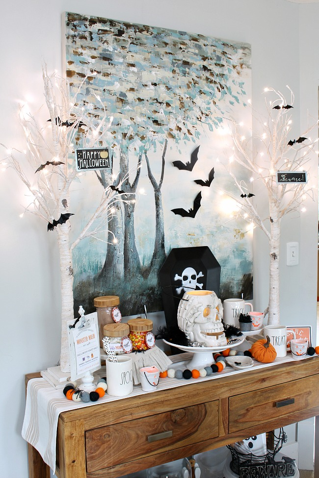 Halloween hot chocolate bar with lighted trees and bats.