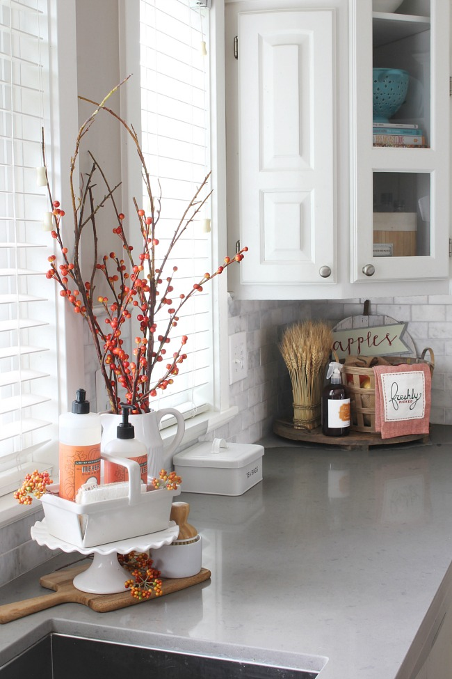 Fall kitchen decor ideas. Faux orange berries and orange dish soap add a pop of color to this white kitchen.