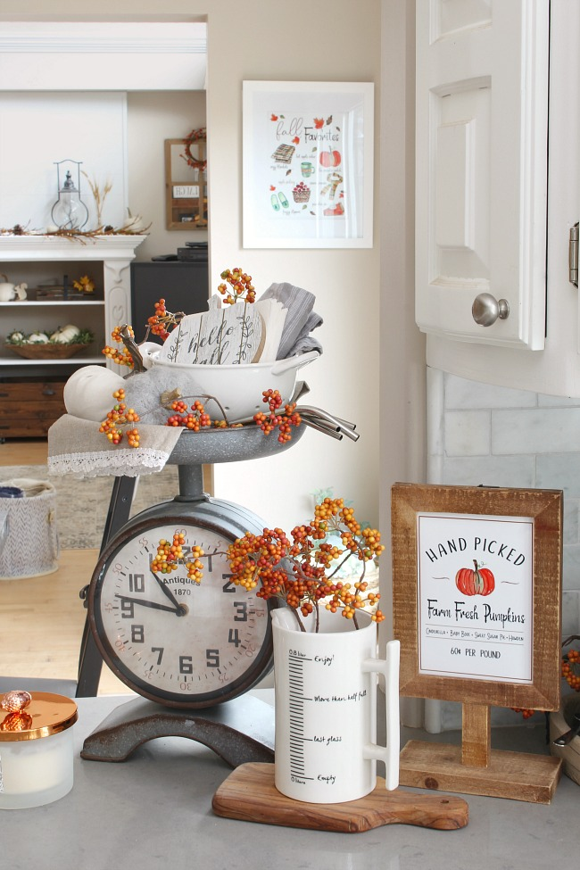 Kitchen scale clock decorated for fall with pumpkins and pops of orange.