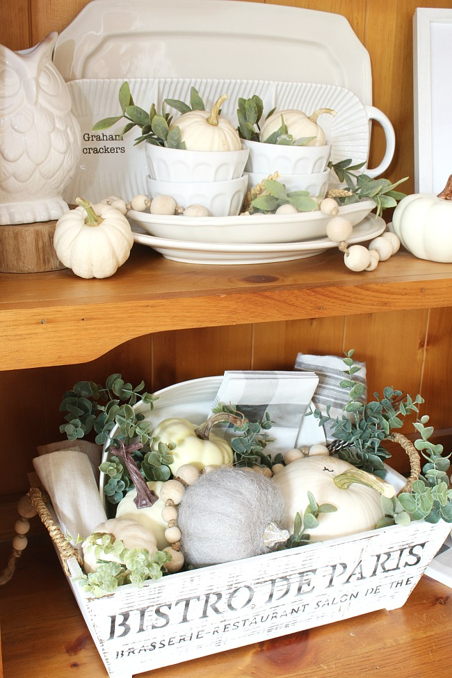 Fall hutch decorated for fall with white ceramics, white pumpkins, and greenery.