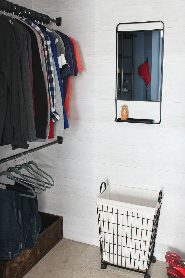 Organized kids closet with a closet organizer system, wire laundry basket, and black framed mirror.