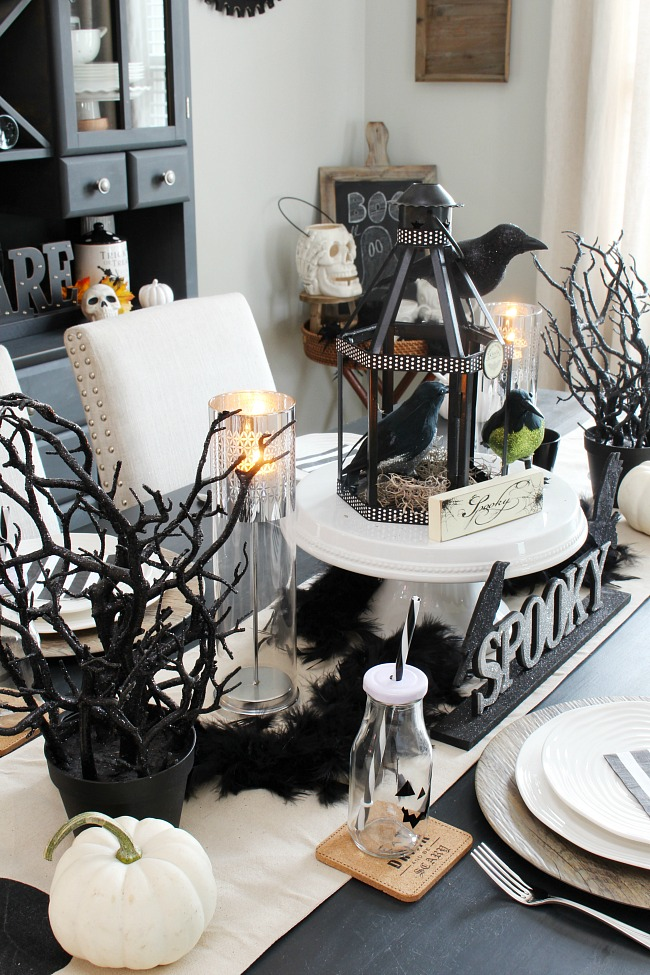 Black and white Halloween decor for a Halloween tablescape. Old lantern used as a spooky birdhouse for the centerpiece.