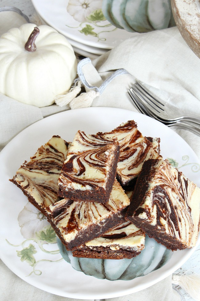 Pumpkin chocolate cream cheese swirl bars on a fall plate.