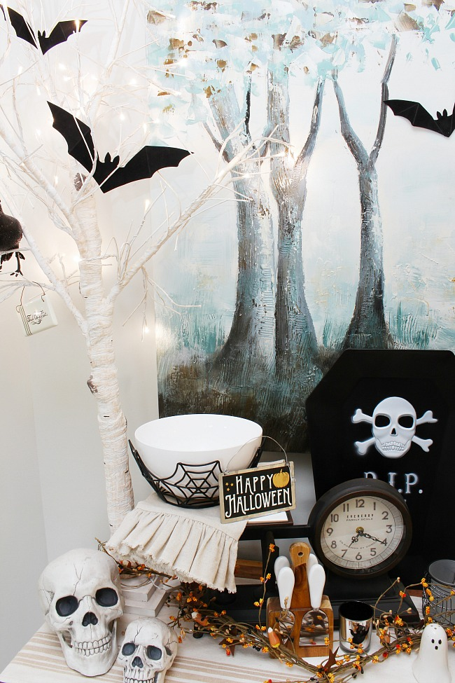 Black and white Halloween decor ideas. Side board decorate with lighted white Christmas trees and black bats.