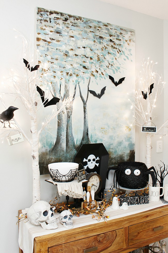 Halloween decor ideas. Sideboard decorated for Halloween using black and white decor and lighted Christmas trees.