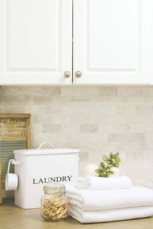 The best laundry tips. Laundry room counter with white towels, laundry bin, and a jar of clothes pegs.