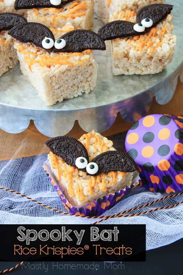 Halloween Rice Krispie treats topped with bats made from cookies and drizzles with orange chocolate.